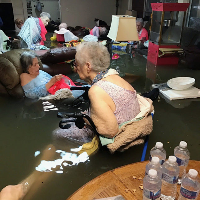 Senior citizens sitting with water surrounding them in nursing home.