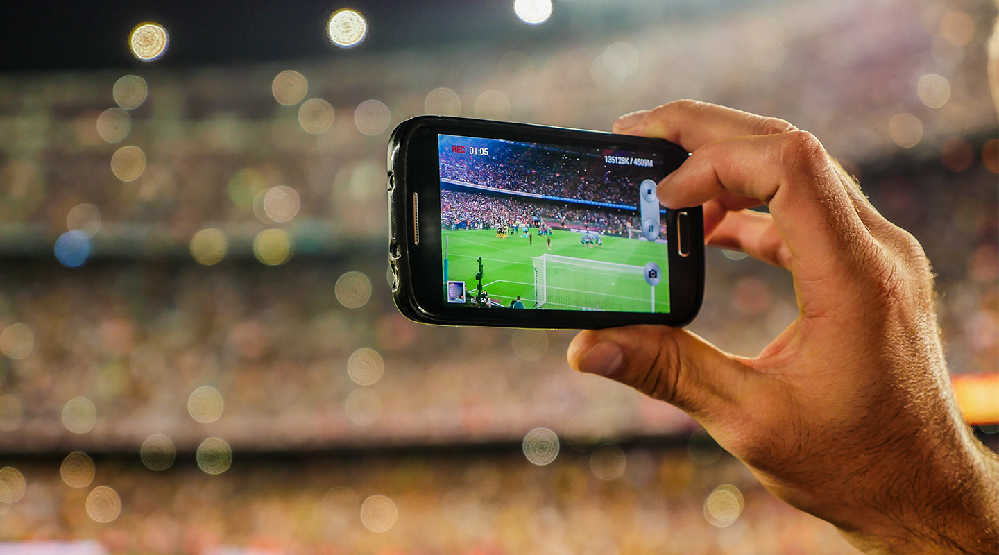 Soccer fan capturing a photo of the field to publish in real-time.