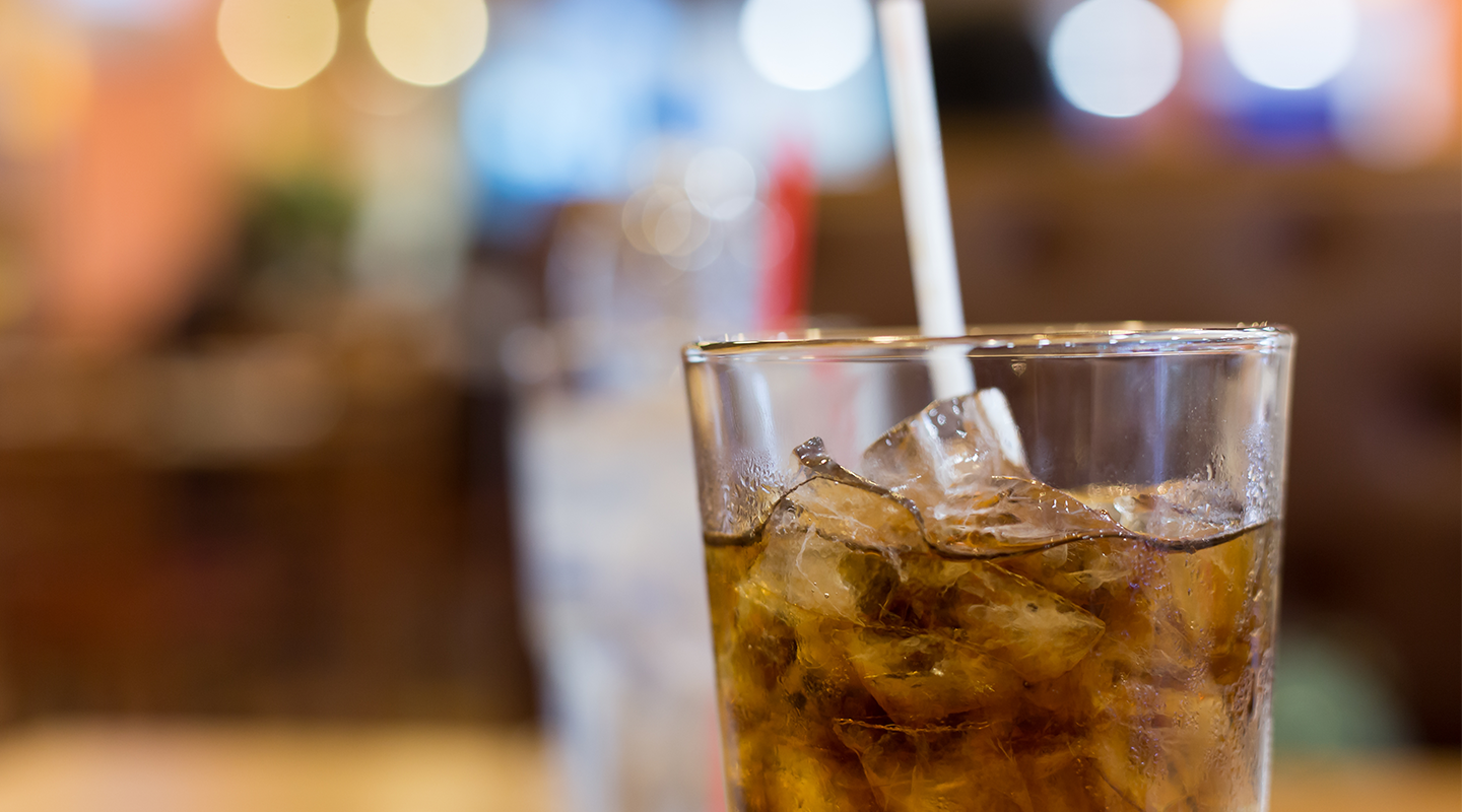 Glass of Pepsi with ice and a straw.
